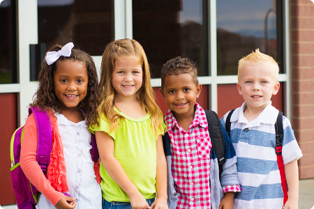 diverse group of young children outside a school